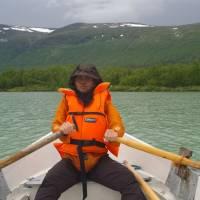 Janča v moskytiéře vesluje přes jezero Lajtaure