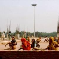 Ruční stavba letištní budovy: ženy ručně uplácavájí beton.