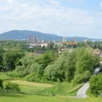 Průmyslový Třinec schovaný v zeleni, vzadu kopec Javorový
